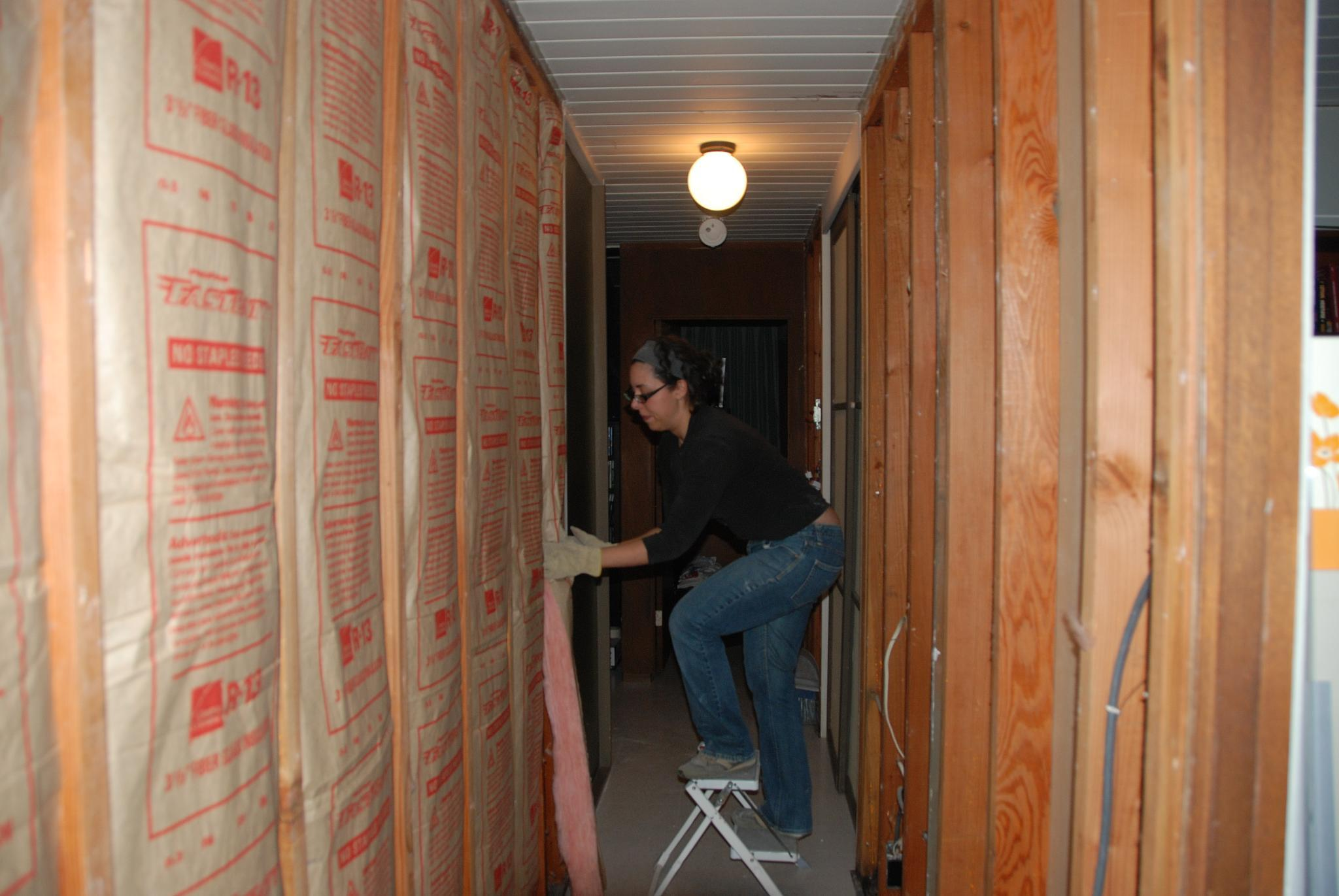Woman installing insulation in her home.